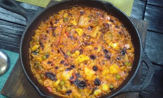 Arroz con pescados y mariscos cocinado a las brasas en sartén de hierro.