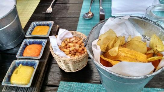 """Picada de patatas y camotes fritos con salsas de ajíes diversos y """"canchitas"""", el maíz frito que se usa para los cebiches."""
